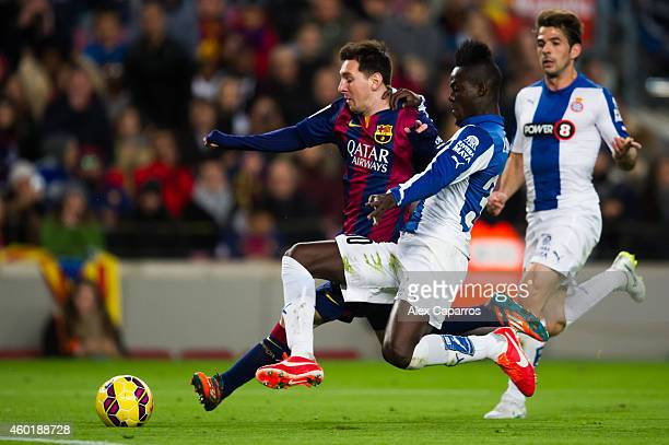 Lionel Messi of FC Barcelona fights for the ball with Eric Bailly of RCD Espanyol during the La Liga match between FC Barcelona and RCD Espanyol at...