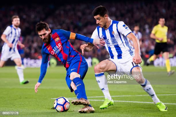 Lionel Messi of FC Barcelona fights for the ball with Yuri Berchiche of Real Sociedad de Futbol during the La Liga match between FC Barcelona and...