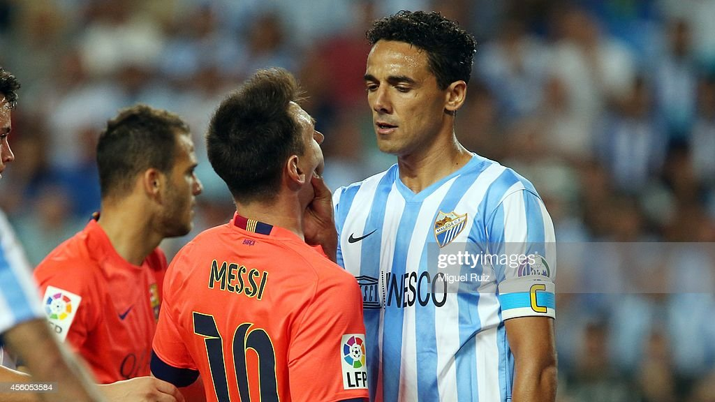 Lionel Messi of FC Barcelona gets fouled by Welingon of Malaga CF during the La Liga match between Malaga CF and FC Barcelona at La Rosaleda Stadium...