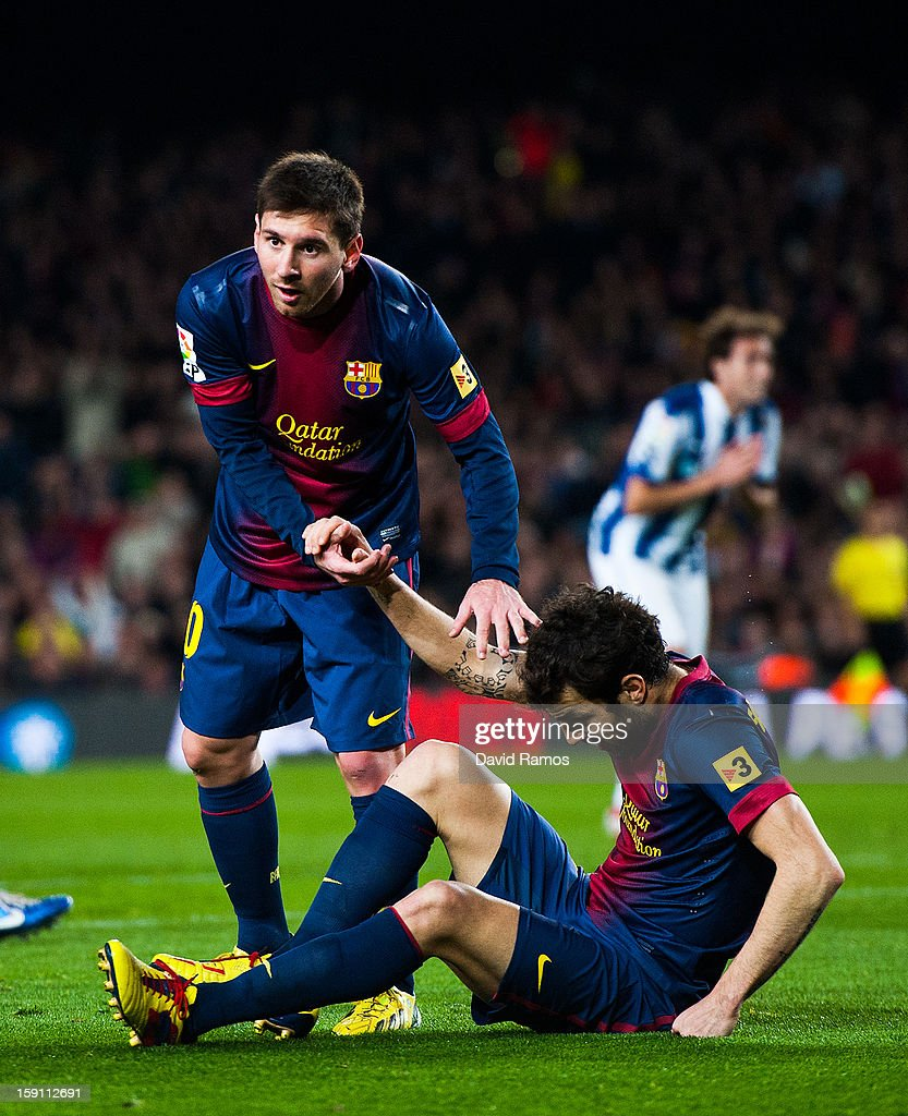 Lionel Messi of FC Barcelona (L) helps his team-mate Cesc Fabregas during the La Liga match between FC Barcelona and RCD Espanyol at Camp Nou on January 6, 2013 in Barcelona, Spain.