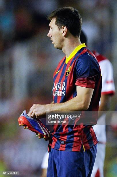 Lionel Messi of FC Barcelona holds his boot during the La Liga match between Rayo Vallecano de Madrid and FC Barcelona at Estadio Teresa Rivero on...