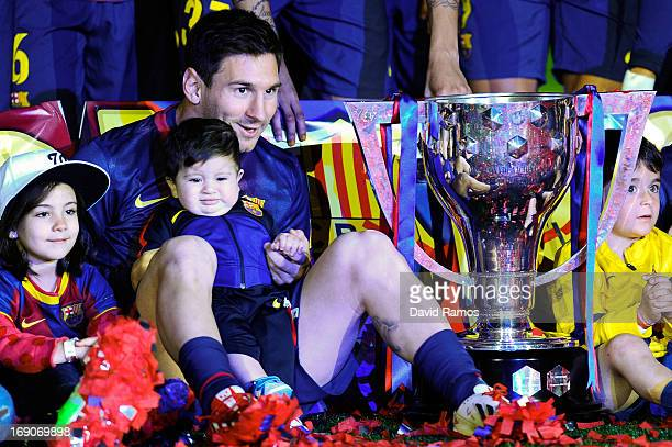 Lionel Messi of FC Barcelona holds his son Thiago as they sit next to the trophy during the celebration after winning the Spanish League after the La...
