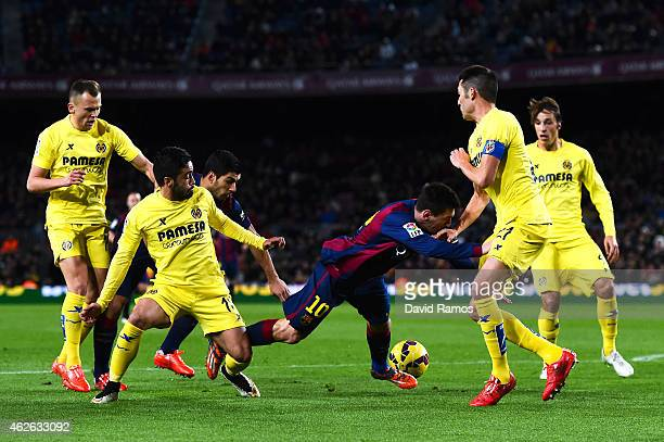 Lionel Messi of FC Barcelona is brought down as he fights for the ball with Villarreal CF players during the La Liga match between FC Barcelona and...