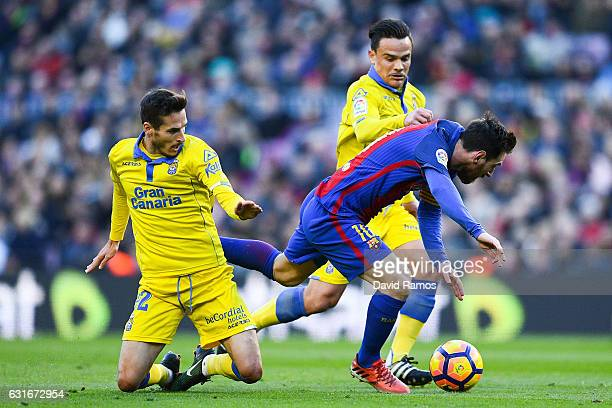 Lionel Messi of FC Barcelona is brought down by Helder Lopes and Roque Mesa of UD Las Palmasduring the La Liga match between FC Barcelona and UD Las...