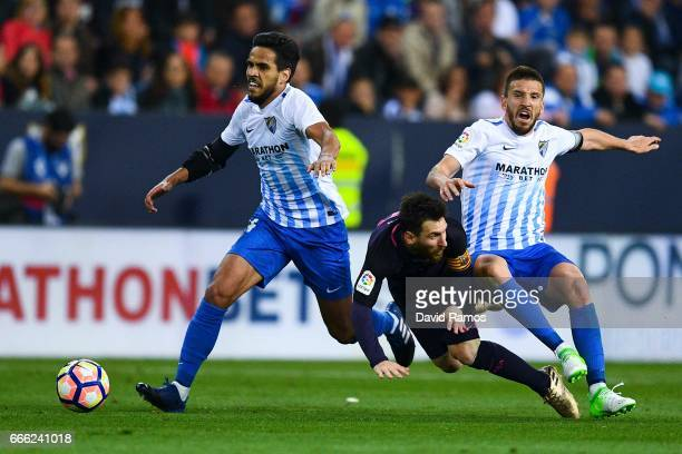 Lionel Messi of FC Barcelona is brought down by Jose Luis Garcia Recio and Ignacio Camacho of Malaga CF during the La Liga match between Malaga CF...