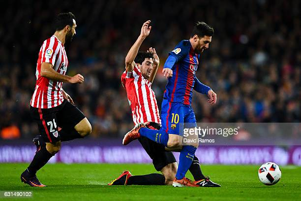 Lionel Messi of FC Barcelona is brought down by Mikel San Jose of Athletic Club during the Copa del Rey round of 16 second leg match between FC...