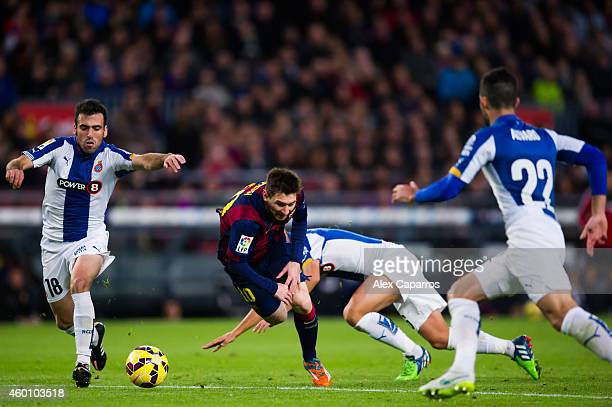 Lionel Messi of FC Barcelona is brought down by Salva Sevilla of RCD Espanyol during the La Liga match between FC Barcelona and RCD Espanyol at Camp...