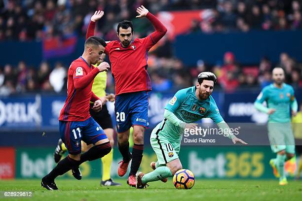 Lionel Messi of FC Barcelona is brought down dy Alex Berenguer and Miguel de las Cuevas of CA Osasuna during the La Liga match between CA Osasuna and...