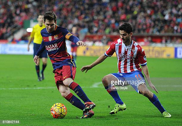 Lionel Messi of FC Barcelona is challenged by Nacho Cases of Sporting Gijon during the La Liga match between Sporting Gijon and FC Barcelona at...