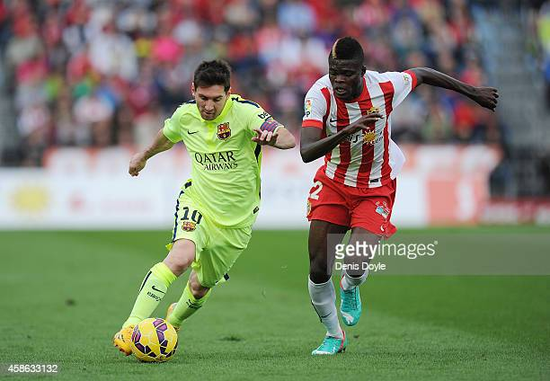 Lionel Messi of FC Barcelona is challenged by Thomas Partey of UD Almeria during the La Liga match between UD Almeria and FC Barcelona at estadio de...