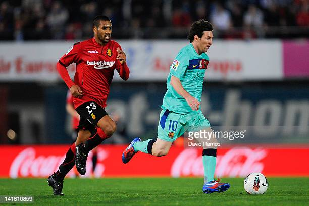 Lionel Messi of FC Barcelona is chased by Fernando Tissone of RCD Mallorca during the La Liga match between RCD Mallorca and FC Barcelona at...