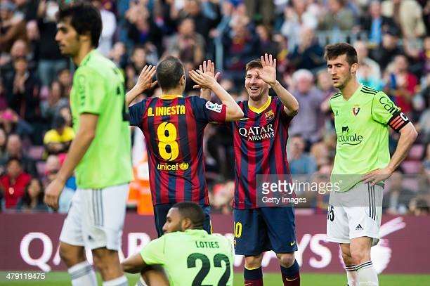 Lionel Messi of FC Barcelona is congratulated by his teammate Andres Iniesta after scoring his team's fourth goal and his goal number 370 for the FC...