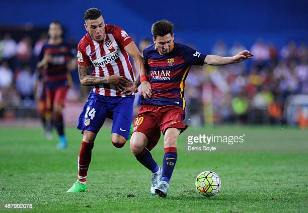 Lionel Messi of FC Barcelona is fouled by Jose Maria Gimenez of Club Atletico de Madrid during the La Liga match between Club Atletico de Madrid and...