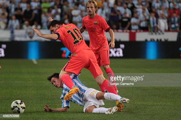 Lionel Messi of FC Barcelona is tackled by Juan Pablo Anor alias Juanpi of Malaga CF during the La Liga match between Malaga CF and FC Barcelona at...