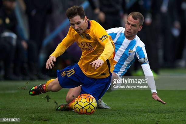 Lionel Messi of FC Barcelona is tackled by Sergio Paulo Barbosa alias Duda of Malaga CF during the La Liga match between Malaga CF and FC Barcelona...