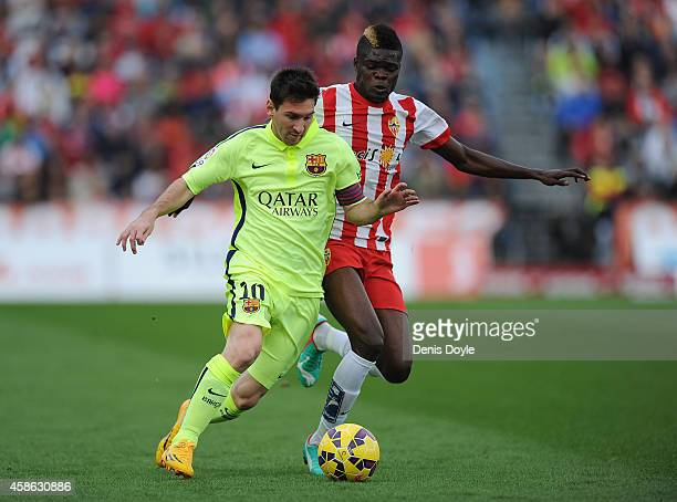 Lionel Messi of FC Barcelona is tackled by Thomas Partey of UD Almeria during the La Liga match between UD Almeria and FC Barcelona at estadio de los...