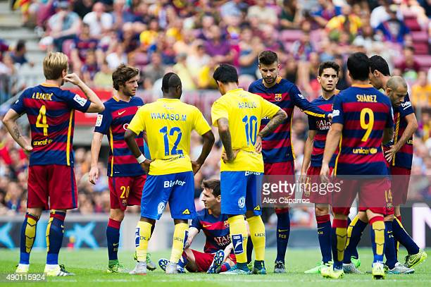 Lionel Messi of FC Barcelona lays injured surrounded by his teammates and players of UD Las Palmas during the La Liga match between FC Barcelona and...