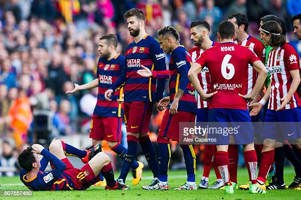Lionel Messi of FC Barcelona lays on the graound after being fouled by Filipe Luis of Club Atletico de Madrid who was shown a red card for this...