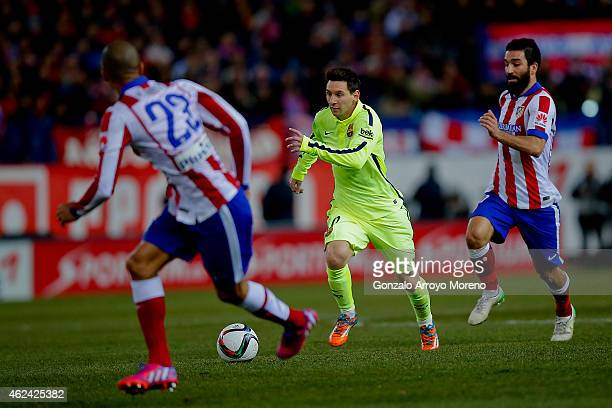 Lionel Messi of FC Barcelona runs for he ball between Arda Turan of Atletico de Madrid and his teammate Joao Miranda during the Copa del Rey Round of...