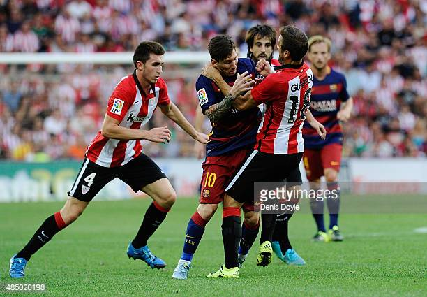 Lionel Messi of FC Barcelona runs into Carlos Gurpegi of Athletic Club during the La Liga match between Athletic Club and FC Barcelona at San Mames...