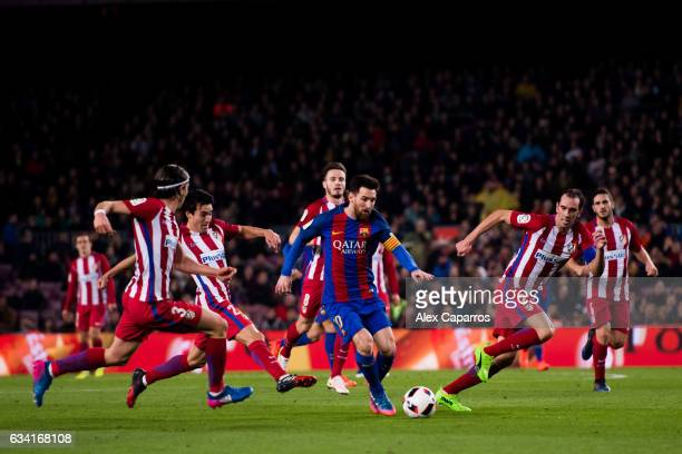 Lionel Messi of FC Barcelona runs with the ball between Filipe Luis Nicolas Gaitan and Diego Godin of Atletico de Madrid during the Copa del Rey...