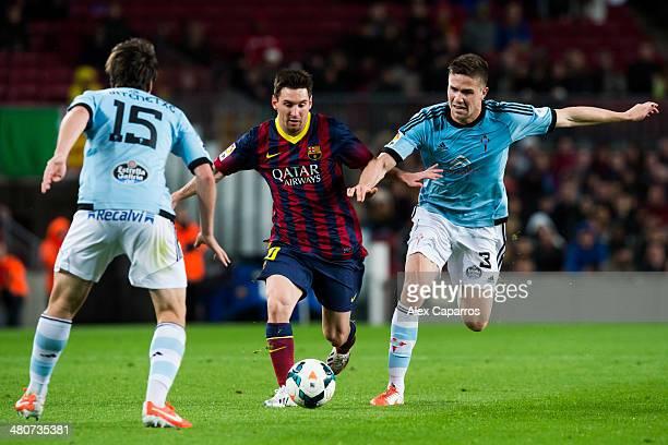 Lionel Messi of FC Barcelona runs with the ball between Jon Aurtenetxe and Andreu Fontas of RC Celta de Vigo during the La Liga match between FC...