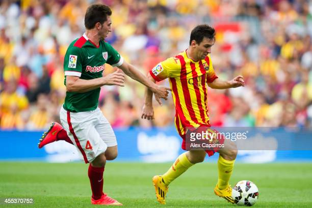 Lionel Messi of FC Barcelona runs with the ball close to Aymeric Laporte of Athletic Club during the La Liga match between FC Barcelona and Athletic...