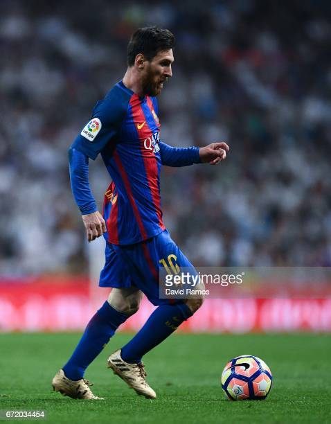 Lionel Messi of FC Barcelona runs with the ball during the La Liga match between Real Madrid CF and FC Barcelona at the Santiago Bernabeu stadium on...