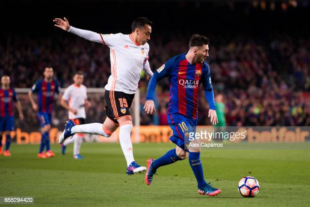 Lionel Messi of FC Barcelona runs with the ball followed by Fabian Orellana of Valencia CF during the La Liga match between FC Barcelona and Valencia...