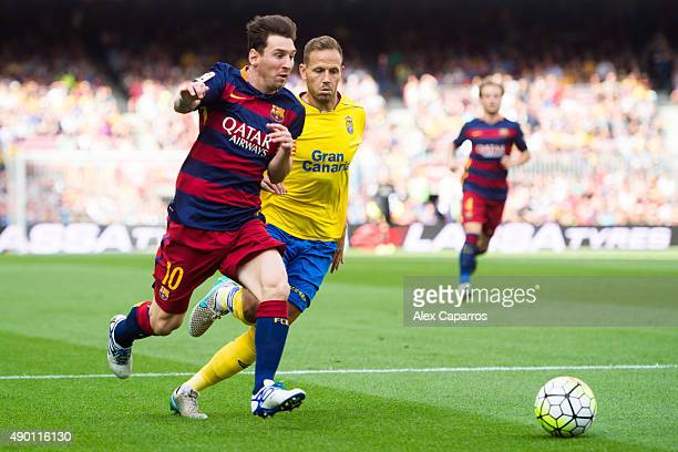Lionel Messi of FC Barcelona runs with the ball next to Daniel Castellano of UD Las Palmas during the La Liga match between FC Barcelona and UD Las...