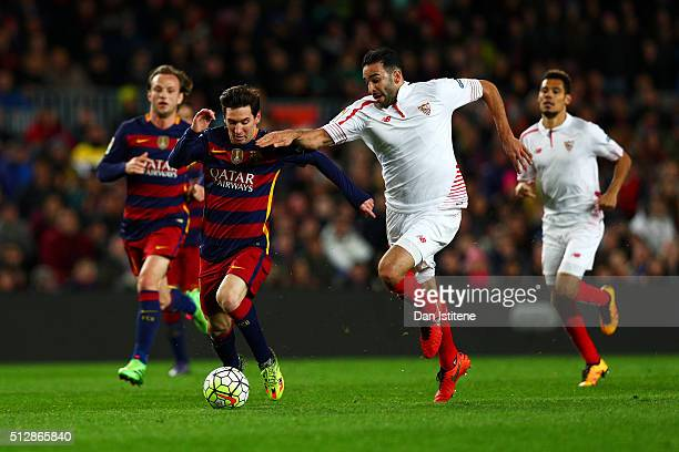 Lionel Messi of FC Barcelona runs with the ball under pressure from Adil Rami of Sevilla FC during the La Liga match between FC Barcelona and Sevilla...