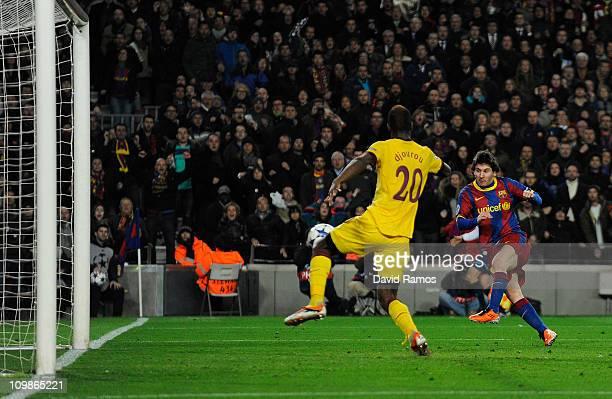 Lionel Messi of FC Barcelona scores his first team's side goal under a chanllenge by Johan Djourou of Arsenal during the UEFA Champions League round...
