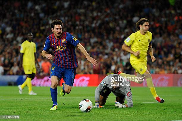 Lionel Messi of FC Barcelona scores his fourth team's goal under a challenge by the goalkeeper Diego Lopez of Villarreal CF during the La Liga match...