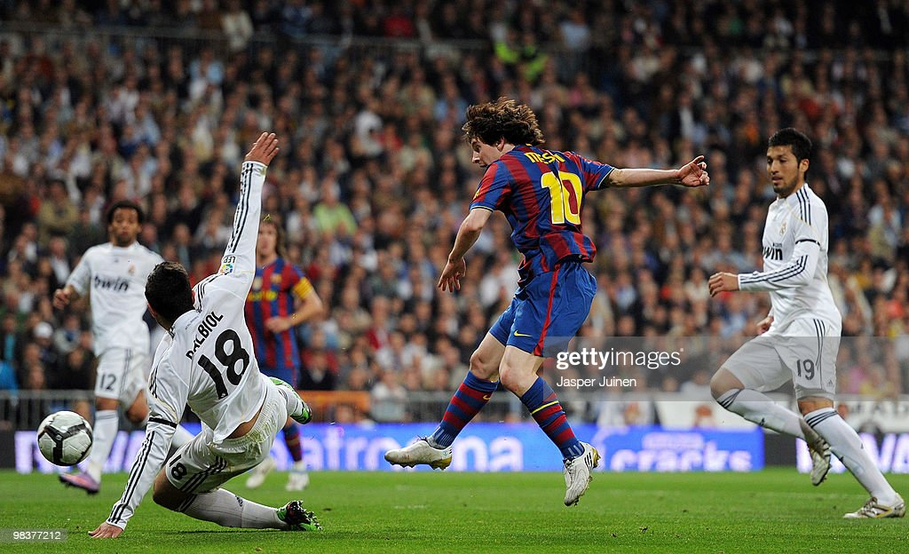 Lionel Messi (C) of FC Barcelona scores his sides opening goal in between Raul Albiol (L) and Ezequiel Garay of Real Madrid during the La Liga match between Real Madrid and Barcelona at the Estadio Santiago Bernabeu on April 10, 2010 in Madrid, Spain.