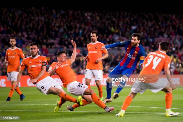 Lionel Messi of FC Barcelona scores his team's fourth goal during the La Liga match between FC Barcelona and CA Osasuna at Camp Nou stadium on April...
