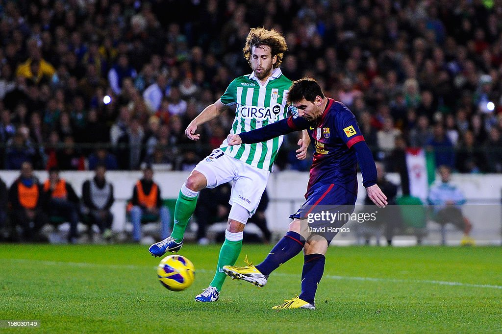 Lionel Messi of FC Barcelona (R) scores his team's second goal past Jose Alberto Canas of Real Betis Balompie during the La Liga match between Real Betis Balompie and FC Barcelona at Estadio Benito Villamarin on December 9, 2012 in Seville, Spain. With this goal Lionel Messi beats the 1972 scoring record set by Gerd Muller of 85 goals in one year.
