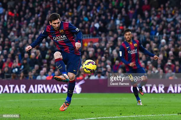 Lionel Messi of FC Barcelona scores his team's third goal during the La Liga match between FC Barcelona and Levante UD at Camp Nou on February 15...