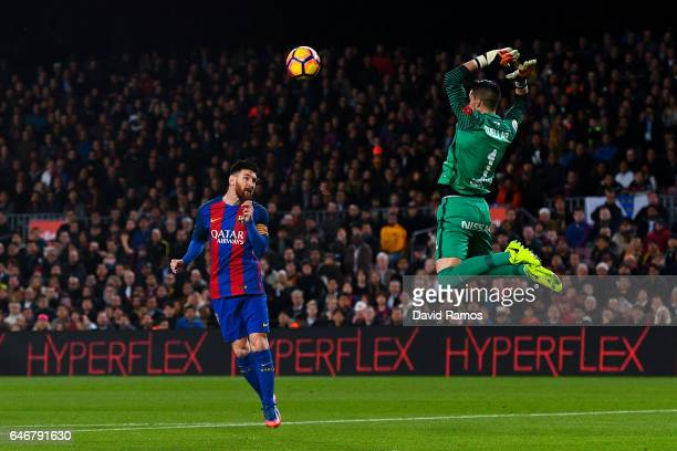 Lionel Messi of FC Barcelona scores the opening goal past Ivan Cuellar of Real Sporting de Gijon during the La Liga match between FC Barcelona and...
