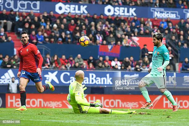 Lionel Messi of FC Barcelona shoots towards goal past Nauzet Perez of CA Osasuna during the La Liga match between CA Osasuna and FC Barcelona at...
