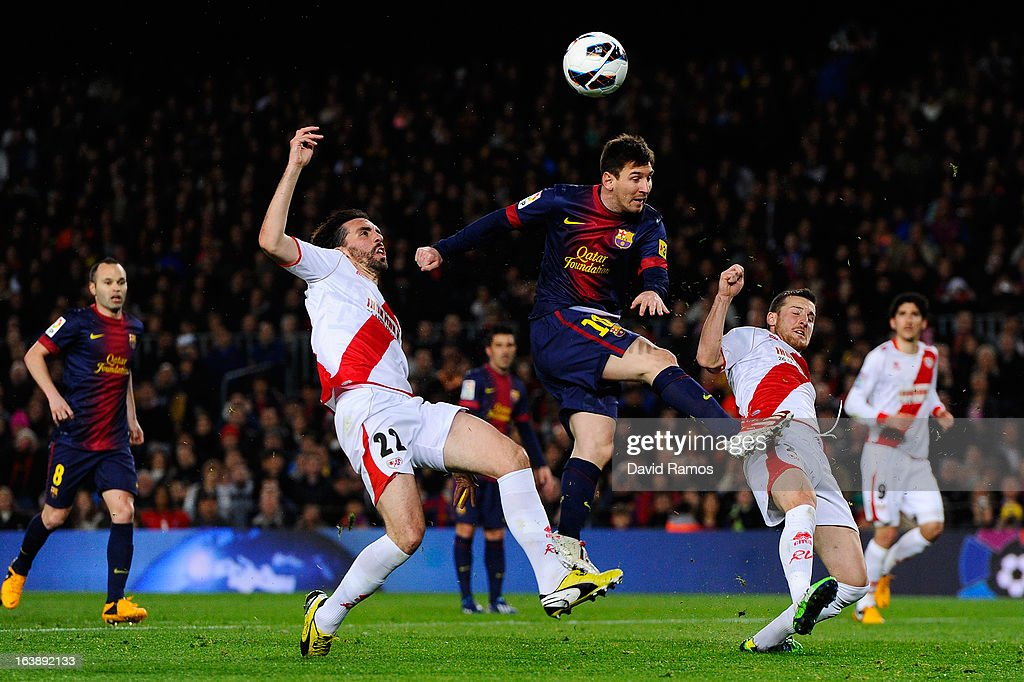 FC Lionel Messi of FC Barcelona shoots towards goal under a challenge by Jordi Figueras (L) and Roberto Roman 'Tito' of Rayo Vallecano during the La Liga match between FC Barcelona and Rayo Vallecano at Camp Nou on March 17, 2013 in Barcelona, Spain.
