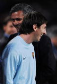 Lionel Messi of FC Barcelona smiles backdropped by Inter Milan coach Jose Mourinho as prepares to watch from the sidelines due to an injury prior to...