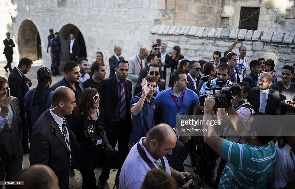Lionel Messi of FC Barcelona waves as he walks through the streets of Bethlehem on August 3, 2013 in Bethlehem, West Bank. Members of the FC Barcelona squad have travelled to the Middle East to visit Israel and the West Bank as part of a two-day 'peace tour'.