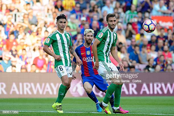 Lionel Messi of FCBarcelona fighting for the ball with Felipe Gutierrez and German Pezzella from Real Betis during the Spanish League match between...