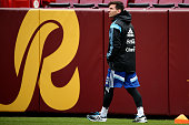 Lionel Messi of the Argentinian national soccer team walks to the bench as his teammates practice on the field in preparation to take on El Salvador...