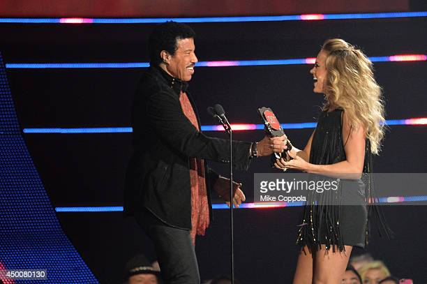 Lionel Richie and Carrie Underwood speak onstage during the 2014 CMT Music awards at the Bridgestone Arena on June 4 2014 in Nashville Tennessee