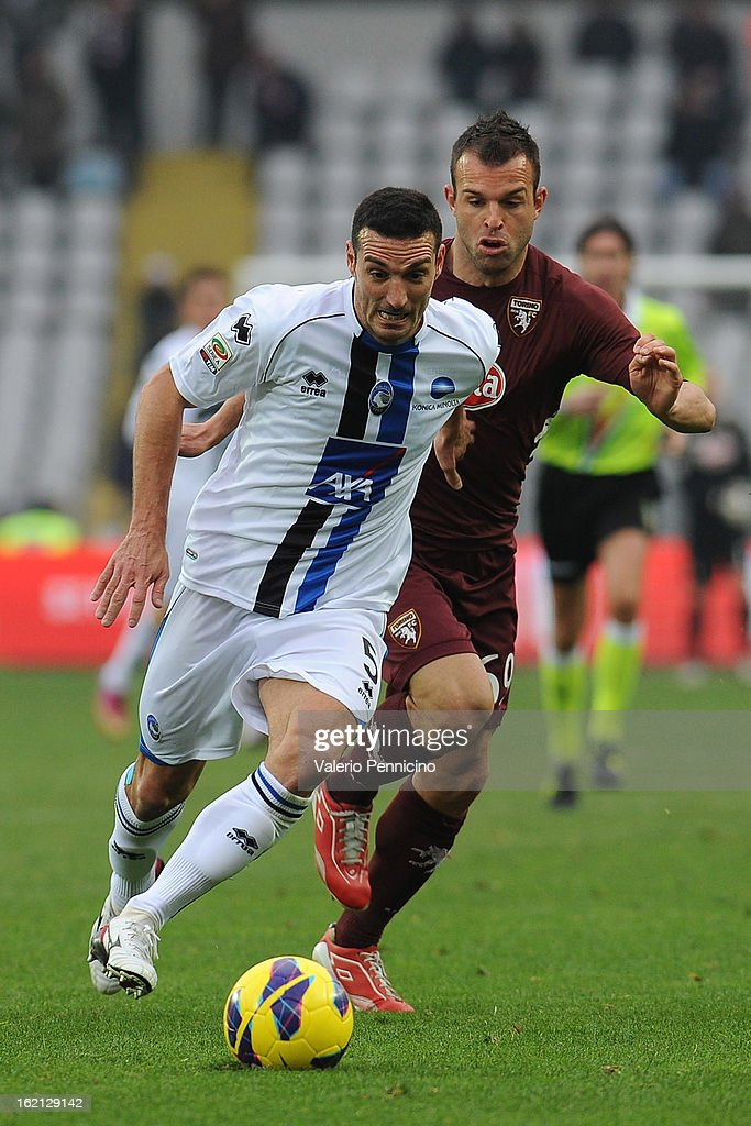 Lionel Scaloni (L) of Atalanta BC takes the ball past Riccardo Meggiorini of Torino FC during the Serie A match between Torino FC and Atalanta BC at Stadio Olimpico di Torino on February 17, 2013 in Turin, Italy.