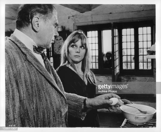 Lionel Stander cracks an egg while Francoise Dorleac watches in a scene from the film 'CulDeSac' 1966