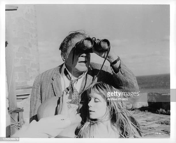 Lionel Stander looking through binoculars as Donald Pleasance and Francoise Dorleac get a close up of each other in a scene from the film 'CulDeSac'...