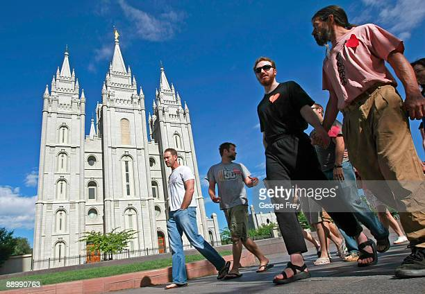 Lionel Trepanier and Lucas Paul walk past the Mormon Temple on the Main Street Plaza holding hands with other protesters July 12 2009 in Salt Lake...