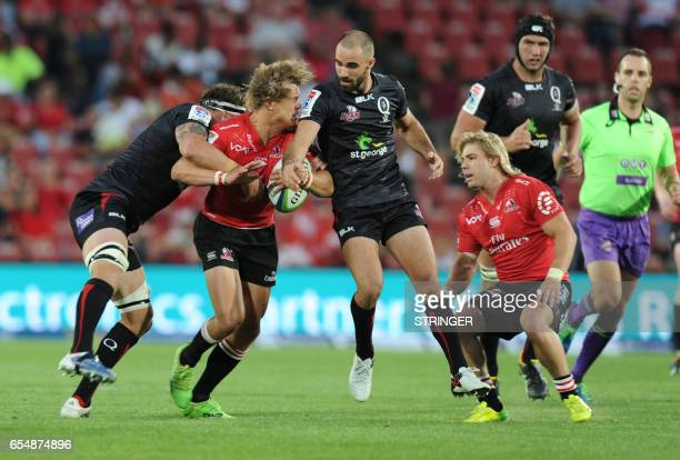 Lions' Andries Coetzee is tackled by Reds' Scott Higginbotham and Nick Frisby during the Super XV rugby match between Lions and Reds at Ellis Park...
